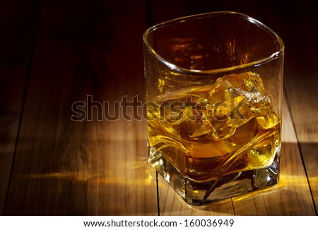 glass of whiskey on wooden table - stock photo