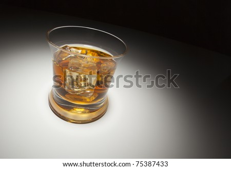 Glass of Whiskey or Other Alcoholic Drink and Ice Under Spot Light. - stock photo