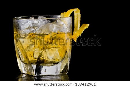 glass of whiskey over ice served on a dark bar garnished with a twist - stock photo