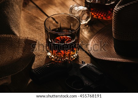 Glass of whiskey, revolver and hat - stock photo