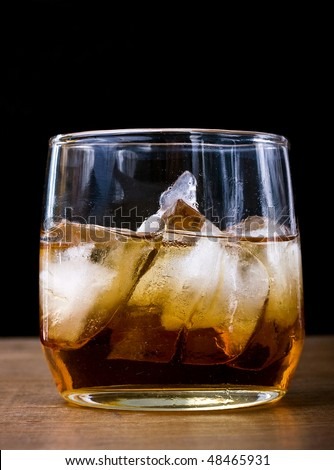 Glass of whiskey, scotch or bourbon on the rocks placed on top of a wooden bar with black background and dark ambiance for vintage look