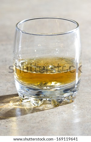 glass of whiskey served neat in a short glass over a light table