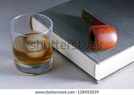 glass of whiskey with a book and a pipe - stock photo