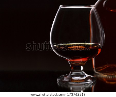 Glass of whiskey with bottle, on dark background, selective focus on the glass with place for text - stock photo