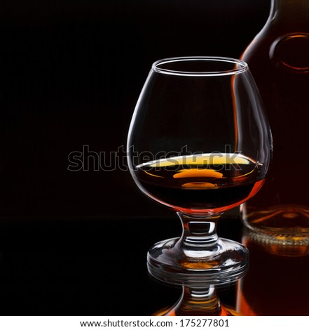 Glass of whiskey with bottle, on dark background with place for text, selective focus on the glass - stock photo