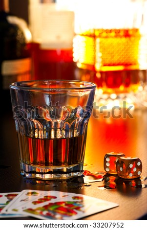 Glass of whiskey with dice and playing cards, shallow DOF - stock photo