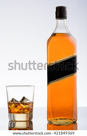 Glass of whiskey with ice and bottle on white background. Whisky on rocks - stock photo