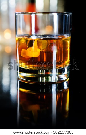Glass of whiskey with ice cubes and fruits - stock photo