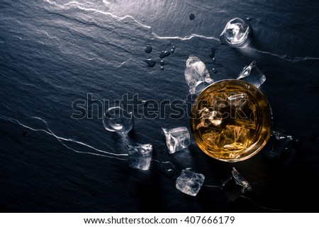 Glass of whiskey with ice cubes on dark table - stock photo
