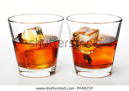 glass of whiskey with ice cubes on white background - stock photo