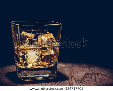 glass of whiskey with ice cubes on wood table, warm atmosphere, time of relax with whisky with space for text - stock photo