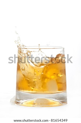 glass of whiskey with ice cubes splashing out over white