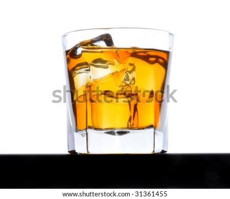 Glass of Whiskey with ice from a low angle on black bar counter white background