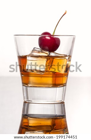 Glass of whiskey with ice, isolated on white background and small depth of field