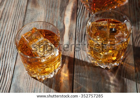 Glass of whiskey with ice on a wooden table
