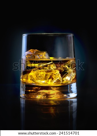 Glass of whiskey with ice on black background - stock photo
