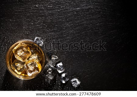 glass of whiskey with ice on black stone table top view with copy space awesome office table top view shutterstock id