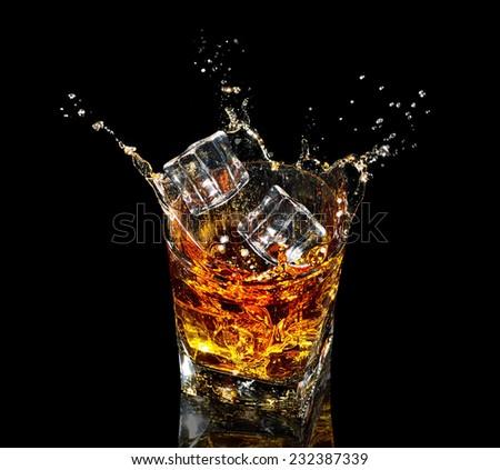 Glass of whiskey with splash on black background - stock photo