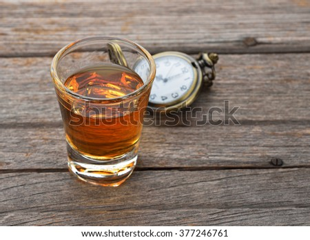 Glass of whisky and Vintage pocket watch on wooden texture