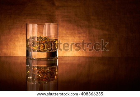 Glass of whisky on a reflective bar-top surface with highlight edging. - stock photo