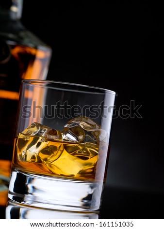 Glass of whisky on the rocks with a bottle