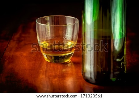 Glass of whisky or rum and a green liquor bottle on a wooden table (with beautiful golden lighting) - stock photo