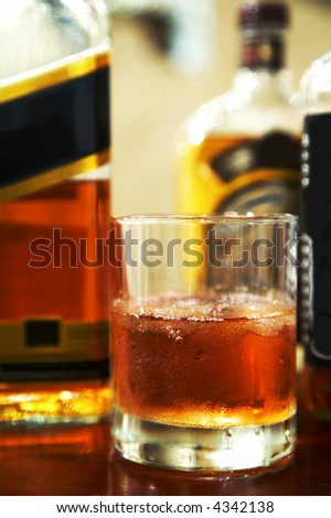 Glass of whisky with an ice and bottles in a bar - stock photo