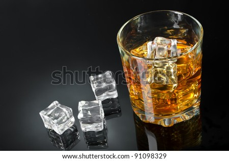 Glass of whisky with ice on a black backdrop - stock photo