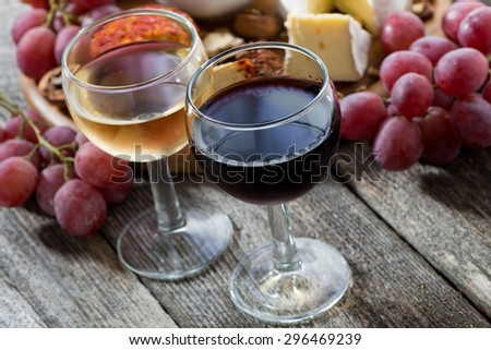 glass of white and red wines, appetizers on a wooden table, top view - stock photo
