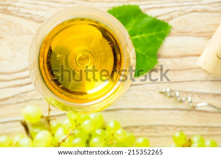 Glass of white wine and a bunch of green grapes, corkscrew and cork. The top view.