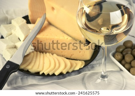 Glass of white wine and assorted cheese with olives on rustic wooden table. Shallow DOF, focus on wine. Toned image. - stock photo