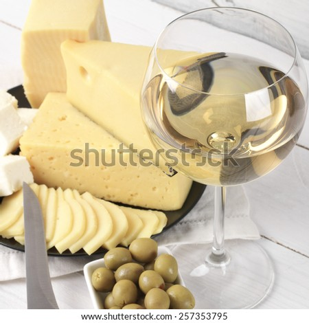 Glass of white wine and assorted cheese with olives on rustic wooden table. Shallow DOF, focus on wine. - stock photo