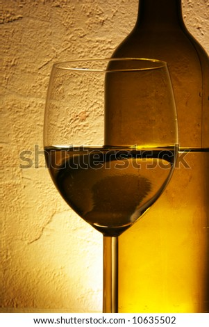 Glass of white wine and bottle close up over yellow background