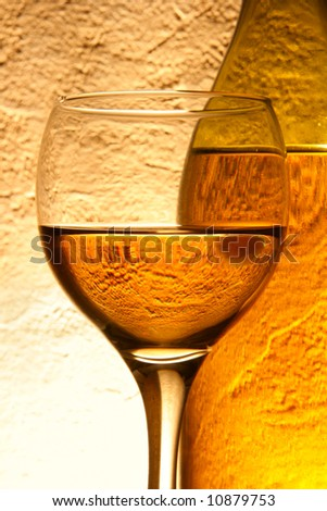 Glass of white wine and bottle over yellow textured background - stock photo