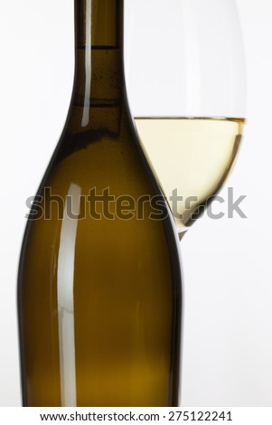 Glass of white wine and brown bottle on the white background