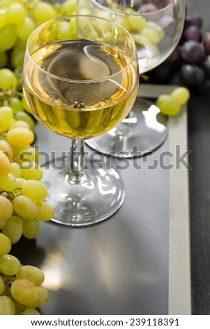glass of white wine and grapes on a blackboard, vertical, close-up - stock photo