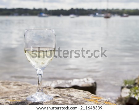Glass of white wine by the coast - stock photo