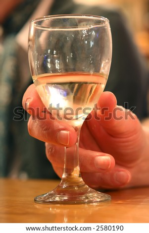 Glass of white wine held in a hand, macro close up