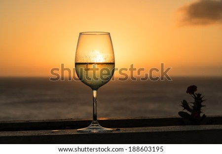 Glass of white wine in the sunset overlooking the sea Curacao caribbean - stock photo