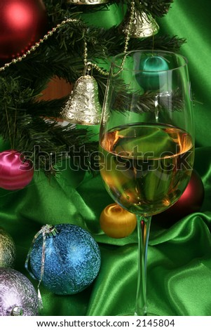 Glass of white wine on a beautiful christmas background with a New Year tree