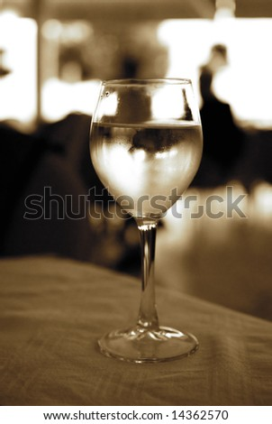 Glass of white wine on a table (toned in sepia) - stock photo