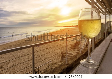 Glass of white wine on a wooden bench overlooking the beach with sunset