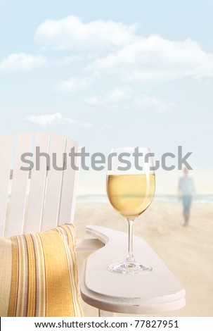 Glass of white wine on adirondack chair at the beach - stock photo