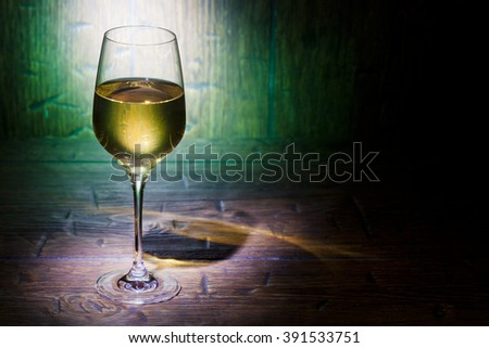 Glass of white wine on green old wooden background with place for text - stock photo