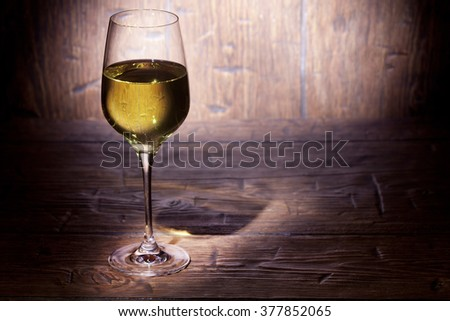 Glass of white wine on old wooden background. With place for text. - stock photo