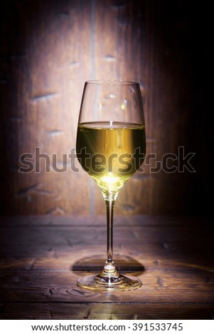 Glass of white wine on old wooden background with place for text - stock photo