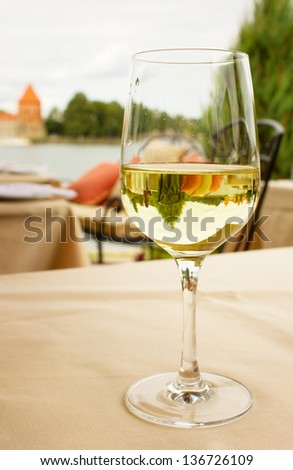 glass of white wine on table in garden