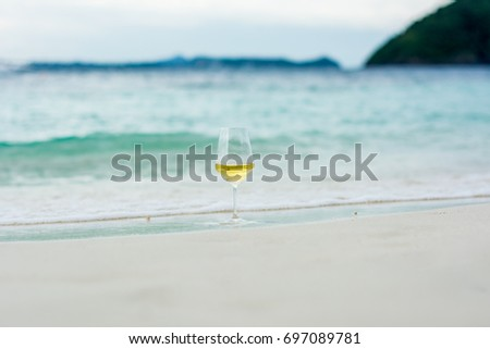 Glass of white wine on the beach at the summer sunny day. Sea on the background. Andaman ocean view at Phuket island, Thailand. Relax time and Travel in vacation concept.