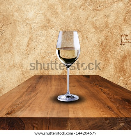 Glass of white wine on wood table - stock photo