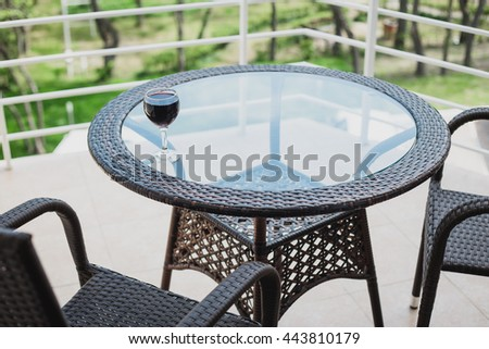 Glass of white wine standing on a table on a cozy terrace - stock photo